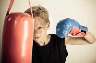 Junge trainiert mit einem Boxsack